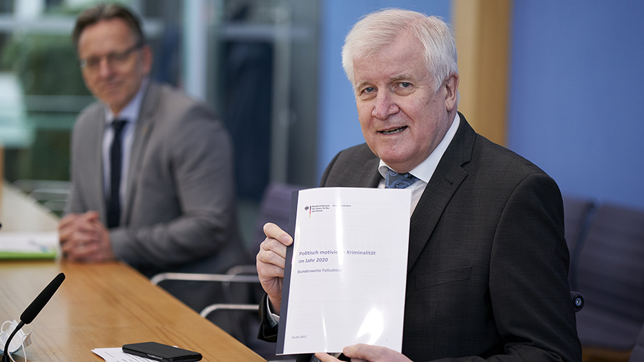 Bundesinnenminister Horst Seehofer sitzt auf dem Podium in der Bundespressekonferenz und hält die PMK in die Kamera. Im Hintergrund sitzt der Präsident des BKA Holger Münch