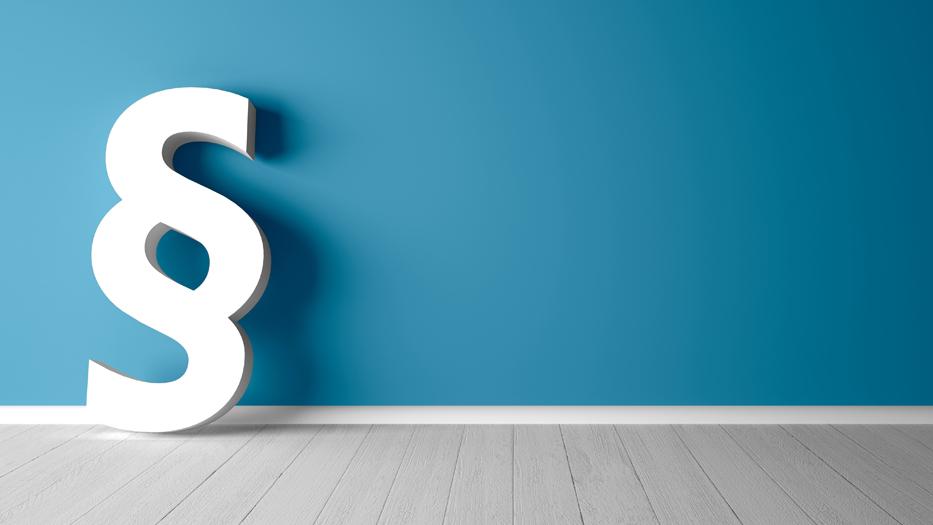 Ein riesiges weißes Paragrafenzeichen lehnt an einer grauen Wand