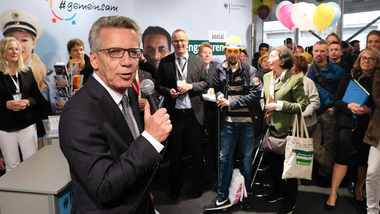 Federal Minister of the Interior Thomas de Maizière visiting the information stand of the Federal Ministry of the Interior