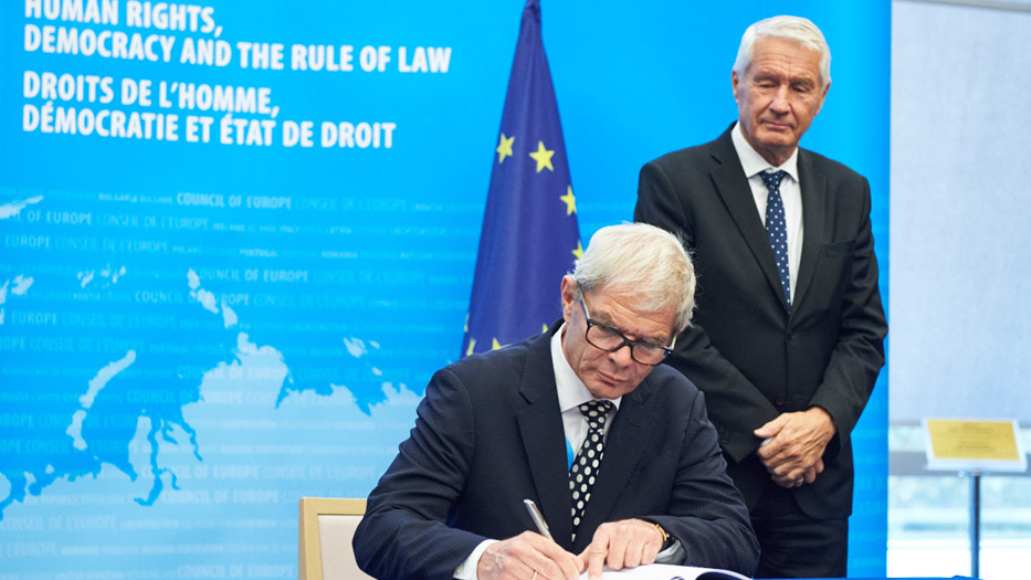 The ambassador of the Permanent Representation of the Federal Republic of Germany to the Council of Europe, Mr Rolf Mafael, signs the Protocol amending. In the background the Secretary General of the Council of Europe Thorbjorn Jagland