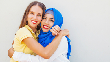 Two women hugging each other. One of them is wearing a headscarf. (refer to: German Islam Conference)