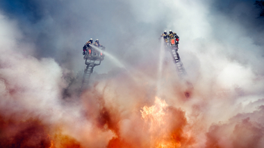 Firefighters stand on turntables and extinguish a big fire (refer to: Police and Emergency Services)