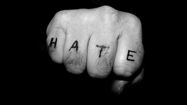 "Clenched fist tattooed with the word ""hate"" (refer to: Extremism)"