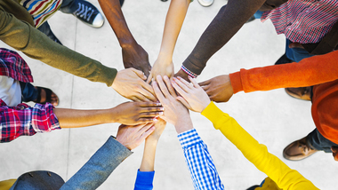 Persons standing in a circle with their hands each on top of the other (refer to: Civic education)