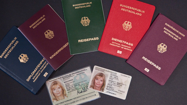 Several different passports as well as the old and new ID card are lying on a black table (refer to: Passports and identity cards)