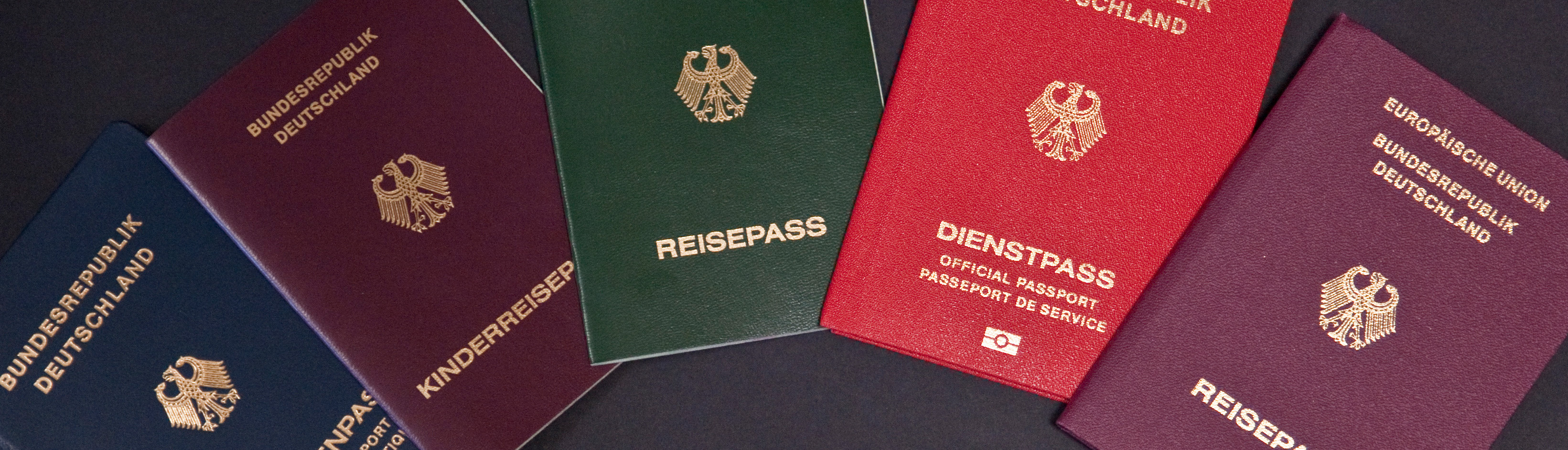 Several different passports as well as the old and new ID card are lying on a black table
