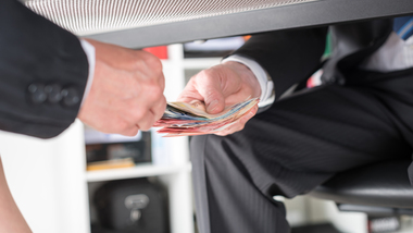 Money being passed from one person to another under a desk (refer to: Integrity)