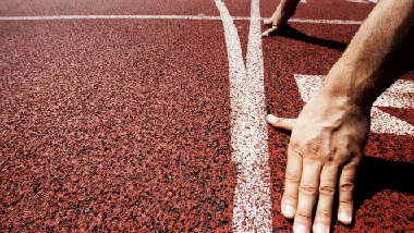 Hand of a runner waiting at the starting line (refer to: Sport funding)